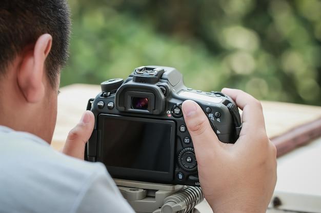 Berufskamera des jungen asiatischen fotografen und einstellung zum fotografieren im hintergrund im freien. hinter den kulissen der aufnahme zum media-dslr-clip auf dem stativ
