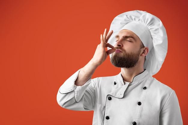 Berufskochmann, der zeichen für köstliches zeigt. männlicher koch in weißer uniform mit perfektem zeichen.