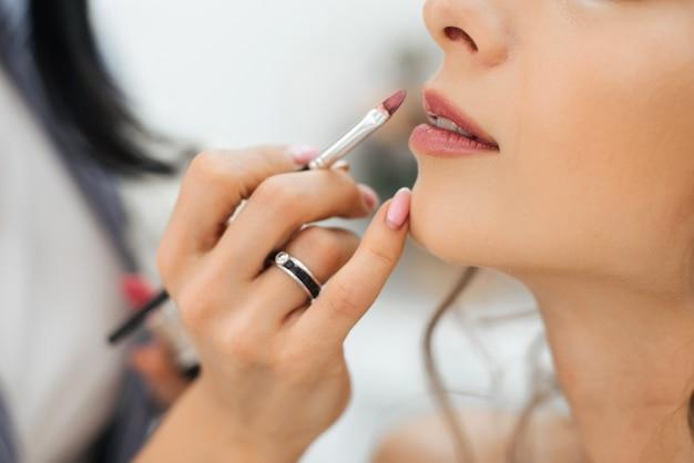 Berufskünstler tut make-up malt lippen mit einem pinsel mit lippenstift auf dem gesicht eines jungen mädchens