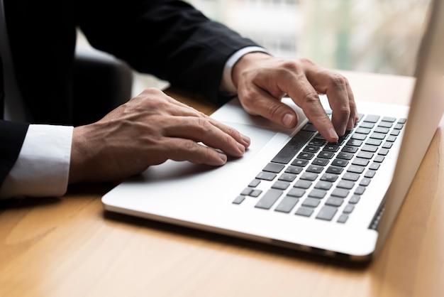 Berufsmann, der auf laptop schreibt