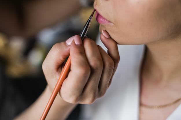 Berufsmaskenbildner, der zu hause mit junger braut, seitenansicht arbeitet
