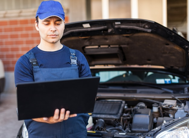 Berufsmechaniker, der eine laptop-computer verwendet, um einen automotor zu überprüfen