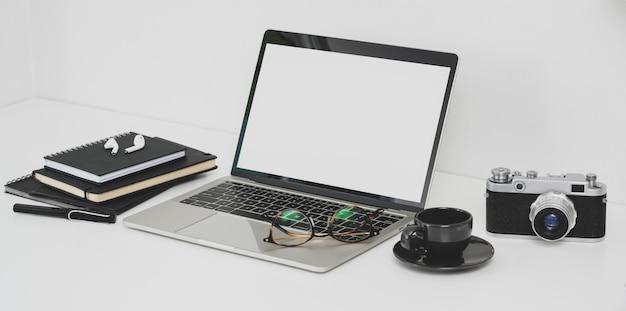 Berufsphotographarbeitsplatz mit offenem laptop, kamera und büroartikel des leeren bildschirms