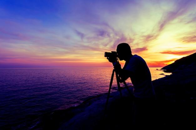 Berufsphotographiemann nehmen einen fotosonnenuntergang oder einen drastischen himmel des sonnenaufgangs über dem tropischen meer in phuket thailand