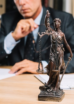 Berufsrechtsanwalt, der am tisch mit gerechtigkeitsstatue in der vordersten reihe sitzt