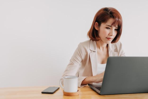 Berufstätige frau benutzt laptop auf dem schreibtisch mit weißem hintergrund