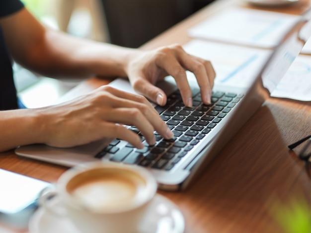 Berufstätige frau, die auf der laptop-tastatur mit finanzbericht und kaffeetasse daneben auf dem schreibtisch tippt