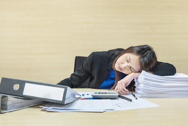 Berufstätige frau, die nach ihr schläft, müde von ihrer arbeit mit arbeitspapier