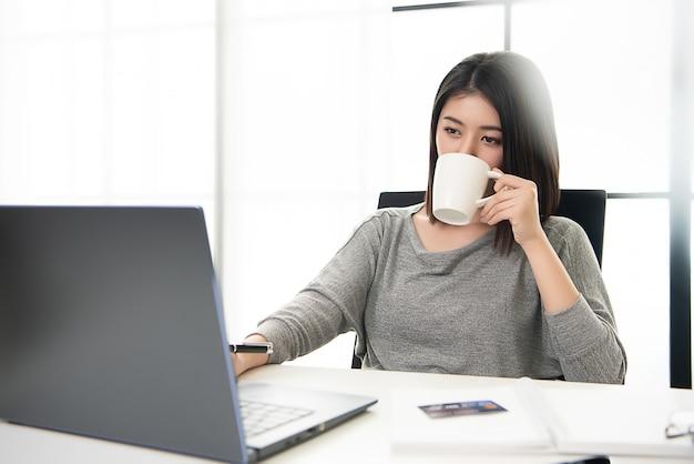 Berufstätige frau, die von zu hause aus arbeitet und kaffee nippt