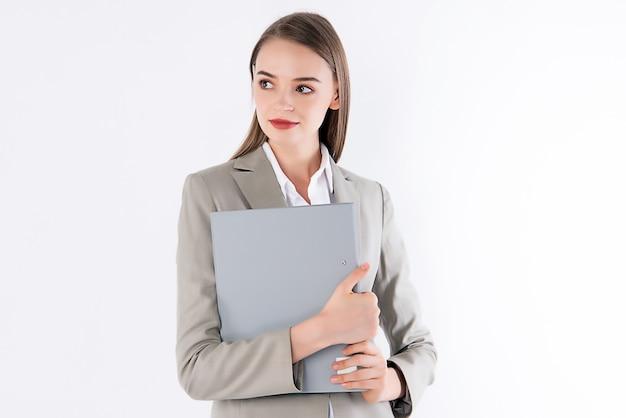 Berufstätige frau hält ihren ordner mit schickem outfit
