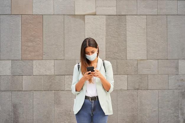 Berufstätige frau in der stadt mit einem smartphone. sie maskiert für die coronavirus-pandemie.