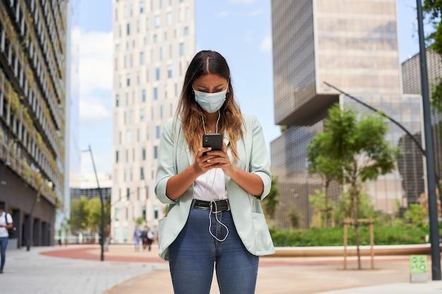 Berufstätige frau in einem finanzzentrum mit einem smartphone mit einer maske für die coronavirus-pandemie.