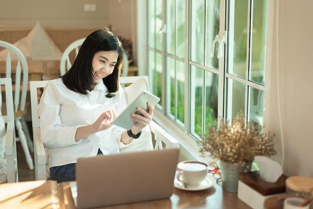 Berufstätige frauen, die mit ipad und laptop im café arbeiten