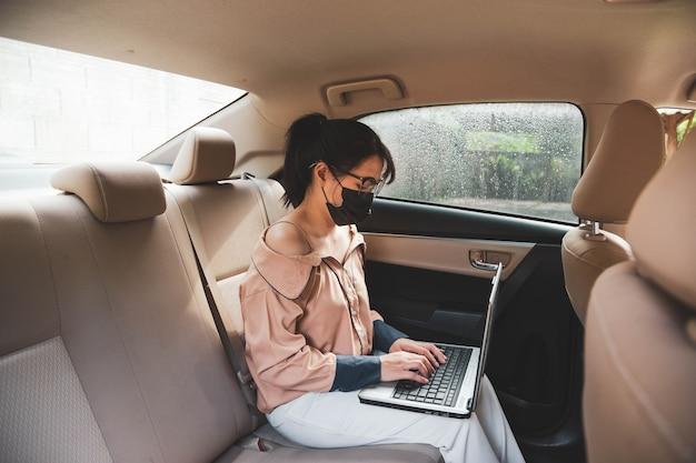 Berufstätige frauen sitzen hinten in einem auto, tragen eine schutzmaske und arbeiten an einem computer