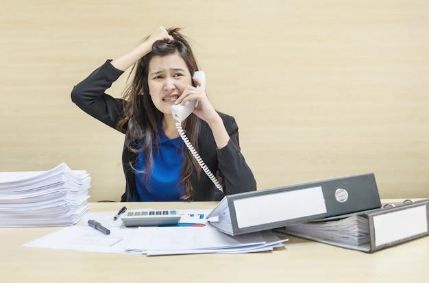 Berufstätige frauen werden aus arbeitspapier und dokumentenakten vor ihr gestresst