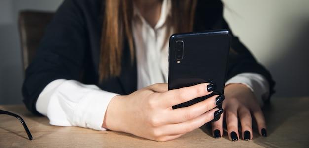 Berufstätige frauenhände mit telefon im büro