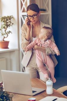 Berufstätige mutter mit baby. junge schöne geschäftsfrau telefoniert mit dem handy und schaut auf den laptop, während sie mit ihrem baby an ihrem arbeitsplatz steht