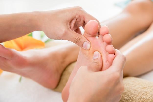 Berufstherapeut, der einer frau im badekurort entspannende reflexzonenmassagefußmassage gibt