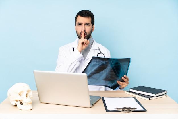 Berufstraumatologe an dem arbeitsplatz, der ein zeichen der ruhegeste einsetzt finger in mund zeigt