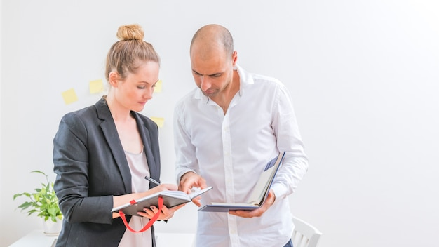Berufswirtschaftler, die zeitplan im tagebuch am arbeitsplatz betrachten