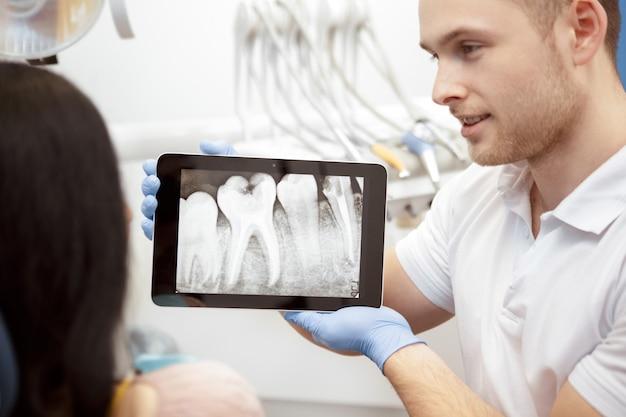 Berufszahnarzt, der seine kundenröntgenstrahlen auf einer digitalen tablette zeigt