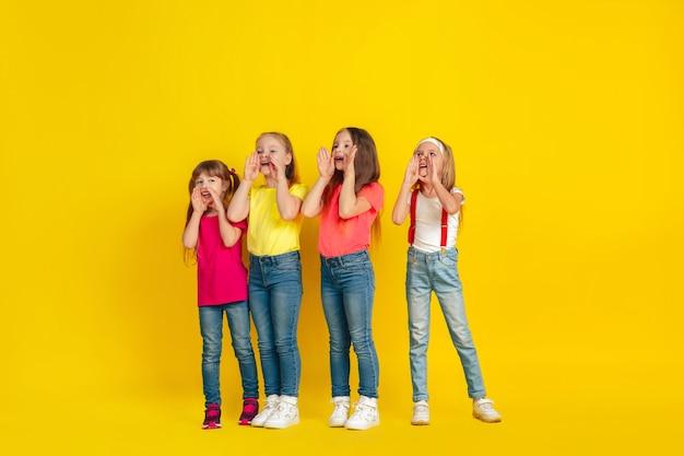 Berufung. glückliche kinder, die zusammen an der gelben studiowand spielen und spaß haben.