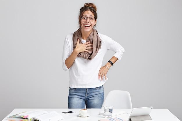 Berufung und kreativität. fröhliche junge erfolgreiche talentierte designerin, die schal und brille stehend trägt