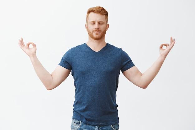 Beruhige dich, frieden im inneren. entspannter gutaussehender europäer mit roten haaren und borsten, schließenden augen, mit gespreizten händen stehenden händen mit zen-geste, meditation, stressabbau mit yoga