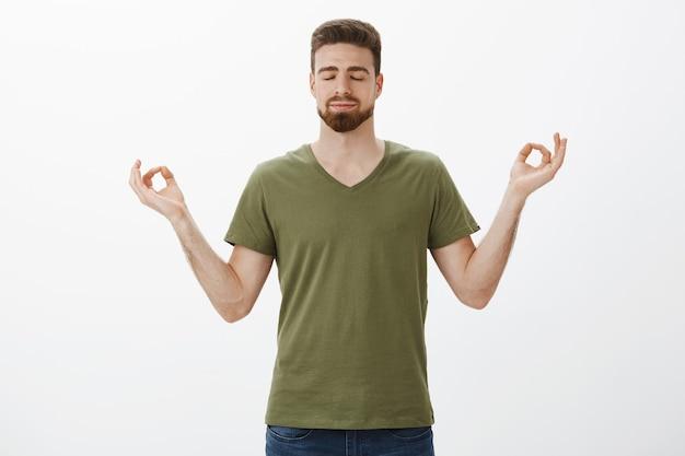 Beruhigen und stress durch meditation abbauen. entschlossener und entspannter attraktiver bärtiger kerl im olivgrünen t-shirt, der hände im lotussitz hält, erreicht nirvana, schließt augen und lächelt entzückt