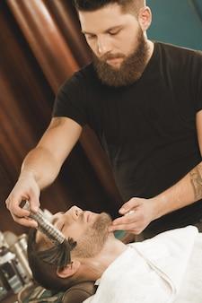 Beruhigende haut nach der rasur. professioneller bärtiger friseur, der puder auf das gesicht seines kunden unter verwendung des friseurpuderpinsels aufträgt