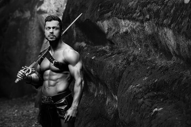Beruhigter krieger. monochrome aufnahme eines gutaussehenden, muskulösen, starken jungen gladiatorenkriegers, der ein schwertexemplar hält holding