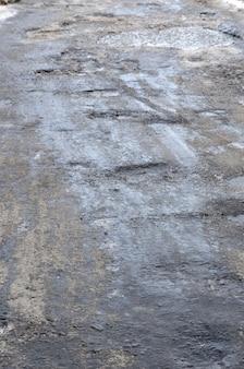 Beschädigte asphaltstraße mit schlaglöchern, die durch einfrieren und auftauen im winter verursacht werden. schlechte straße