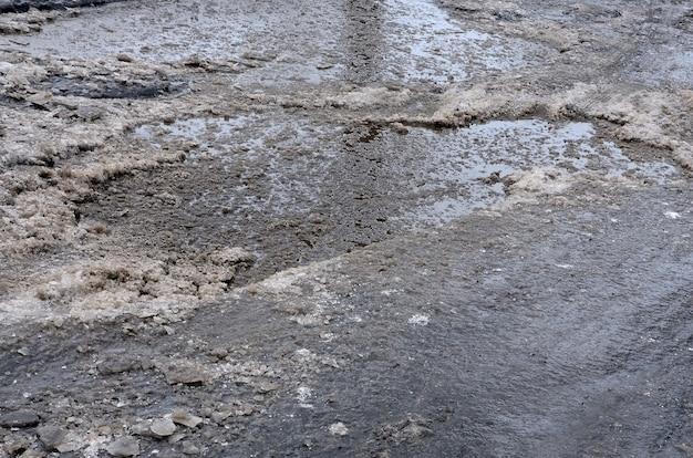 Beschädigte asphaltstraße mit schlaglöchern, die durch einfrieren und auftauen im winter verursacht werden