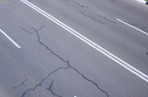 Beschädigte schlechte asphaltstraße mit schlaglöchern.