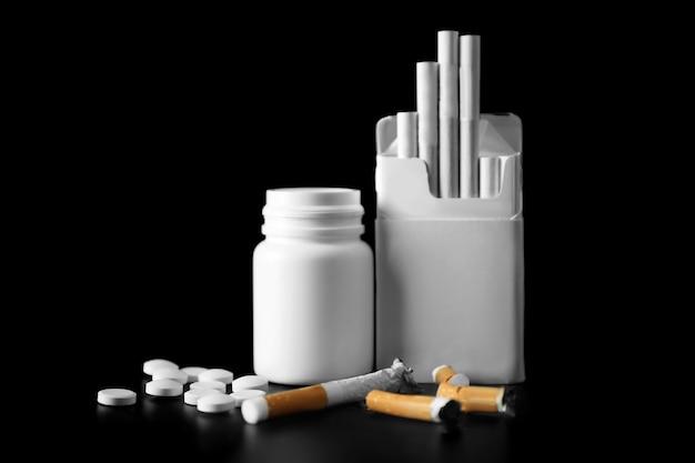 Beschädigte zigaretten, packung und drogen auf schwarzem hintergrund