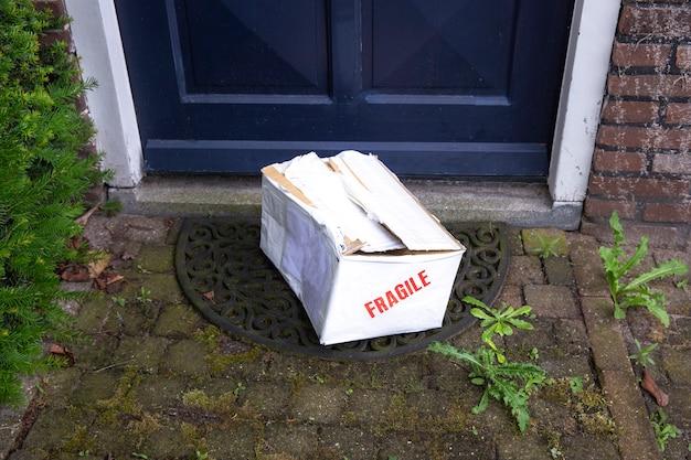 Beschädigter lieferkarton an der haustür eines zerbrechlichen pakets mit dellen, schlechte lieferung