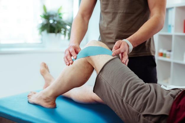 Beschädigtes bein. nahaufnahme eines männlichen beins mit einem blauen gummiband darauf