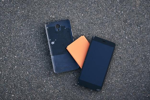 Beschädigtes smartphone mit kaputtem touchscreen auf dem asphalt