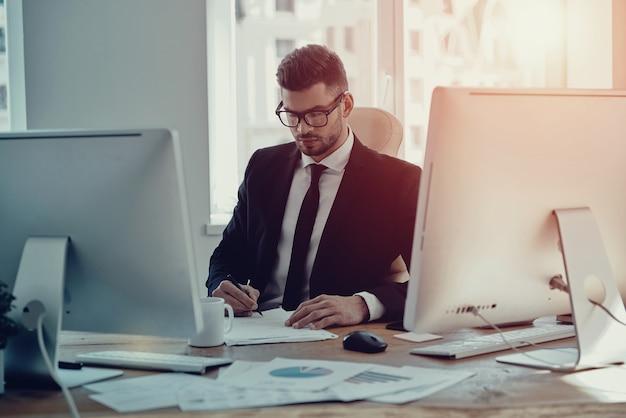 Beschäftigt mit papierkram. schöner junger mann in abendkleidung, der die formulare ausfüllt, während er im büro sitzt sitting