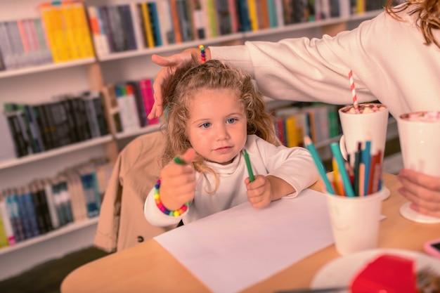 Beschäftigt sein. freundliches baby, das ellbogen auf tisch lehnt, während man bild zeichnet