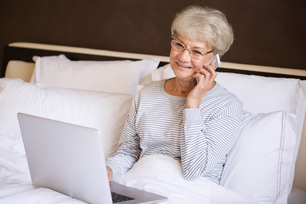 Beschäftigte ältere frau, die im bett arbeitet