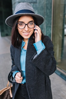 Beschäftigte arbeitszeit der modischen jungen frau im grauen mantel, im hut, in der schwarzen brille, die auf straße in der stadt geht. telefonieren, lächeln, geschäftsfrau, luxus-lifestyle.