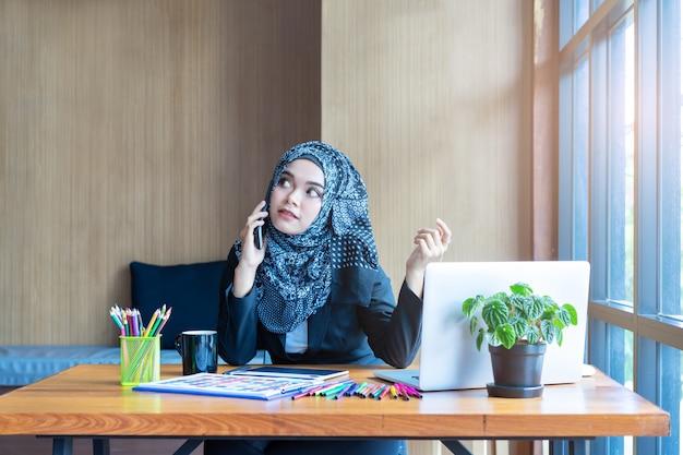 Beschäftigte asiatische moslemische geschäftsfrau, die am handy im modernen büro spricht.