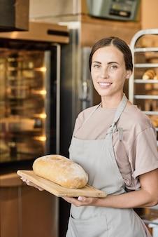 Beschäftigte bäckerin in schürze, die mit frischem weißbrot auf holzbrett am arbeitsplatz steht