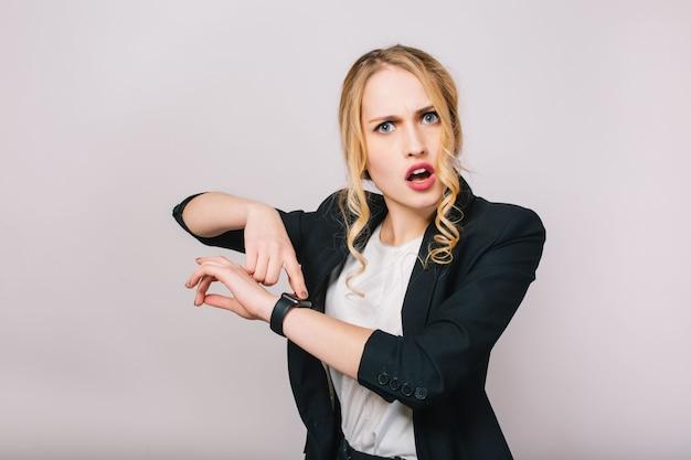 Beschäftigte büroarbeitszeit der erstaunten jungen blonden frau im weißen hemd und in der schwarzen jacke, die isoliert suchen. treffen, zuschauen, zu spät kommen, arbeiter, job, manager
