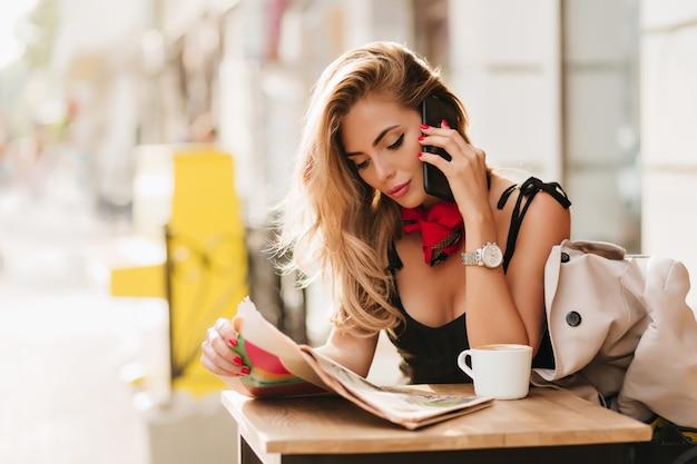 Beschäftigte dame in stilvoller kleidung, die freund anruft, während artikel in frischer zeitung liest