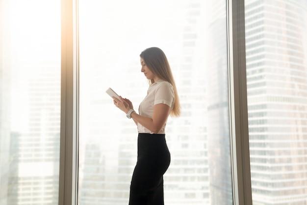 Beschäftigte ernste geschäftsfrau, die die digitale tablette, stehend nahe großem fenster verwendet