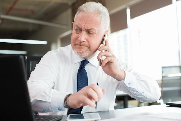 Beschäftigte exekutivlese-email und am telefon sprechend