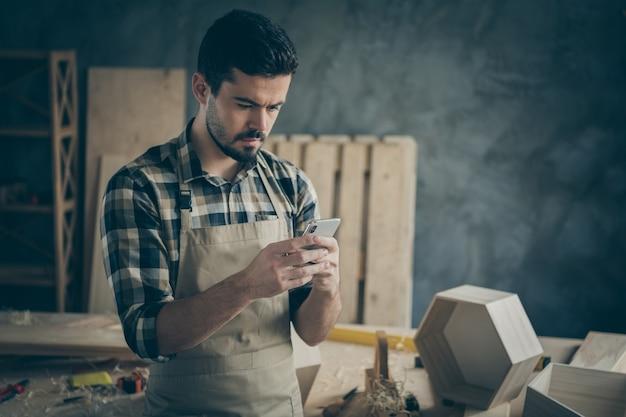 Beschäftigte fokussierte hartholzarbeiter verwenden seinen smartphone-text mit angeboten für kundenrestaurierungsaufträge in der garage des hauses