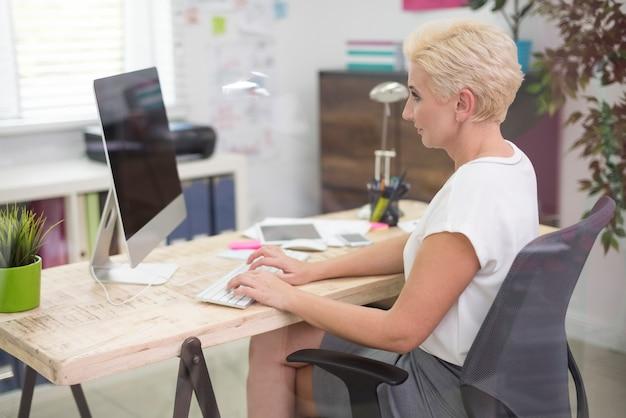 Beschäftigte frau, die am computer arbeitet